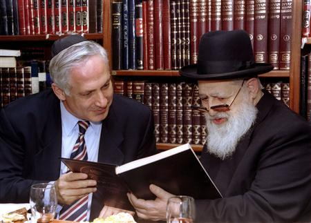 Then Israeli Prime Minister-elect Benjamin Netanyahu (L) and Rabbi Ovadia Yosef read the dedication of a Jewish religious book given to Netanyahu by Yosef during a meeting in this June 13, 1996 file photo.