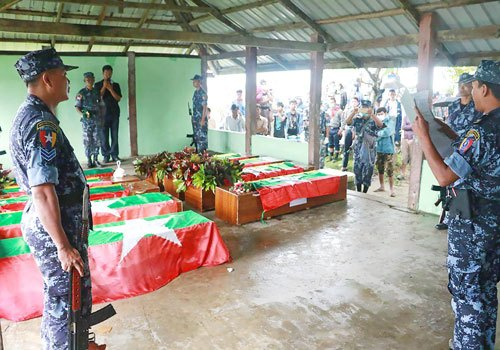Myanmar Border Police on October 11 prepare the flag-draped coffins bearing nine bodies of border guards killed two days earlier.AFP